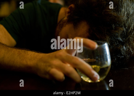 Man at bar with glass of whisky resting head on arms - Stock Photo