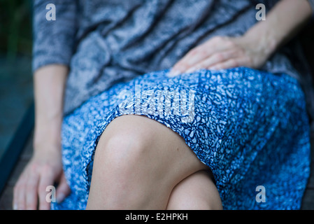 Woman sitting with legs crossed, cropped - Stock Photo