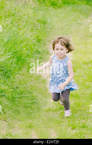 Little girl running on path through countryside - Stock Photo