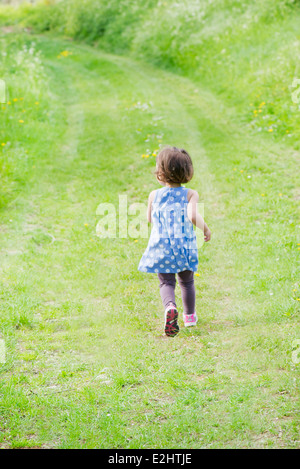 Little girl running on path through countryside, rear view - Stock Photo