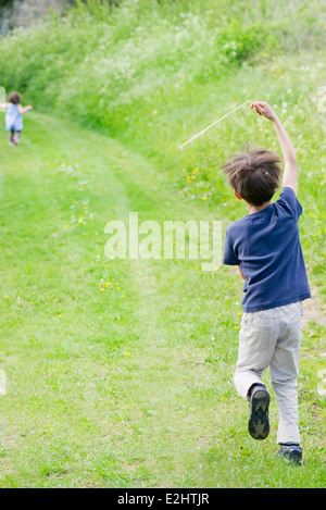 Boy running on country path, rear view - Stock Photo