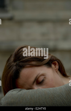 Woman resting head on arms - Stock Photo