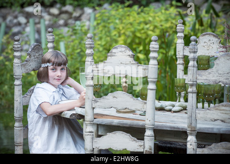 Girl sitting at dining table outdoors - Stock Photo