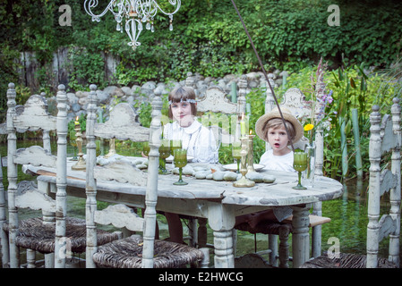Children playing make-believe outdoors - Stock Photo