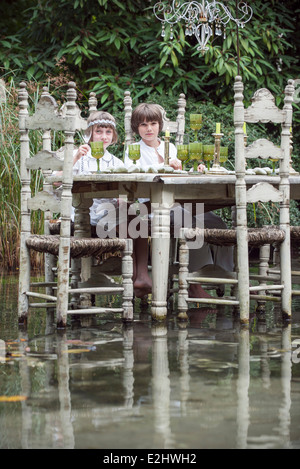 Children seated at dining table floating on lake - Stock Photo