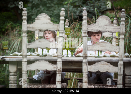 Children seated at dining room table outdoors - Stock Photo