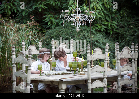 Children seated at ornate dining table outdoors - Stock Photo