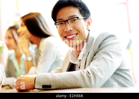 Portrait of smiling businessman sitting in front of colleagues - Stock Photo