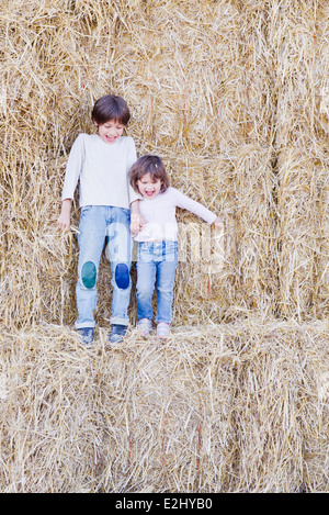 Young siblings standing on hay bales, holding hands - Stock Photo