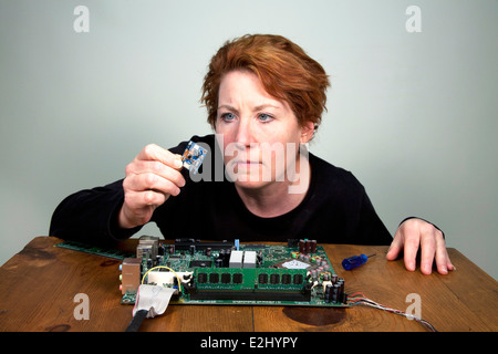 Female engineer examining computer chip removed from a laptop motherboard. - Stock Photo