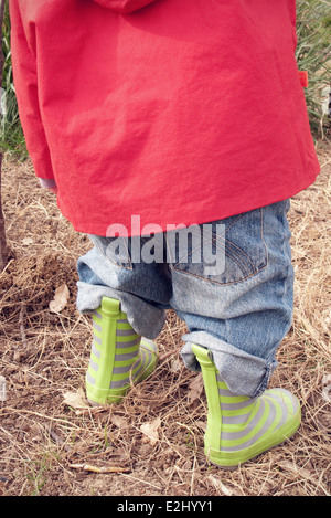 Child wearing raincoat and rubber boots, cropped - Stock Photo