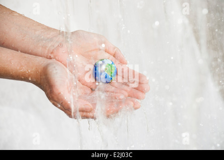 Ecology concept, child's hands holding earth under waterfall - Stock Photo