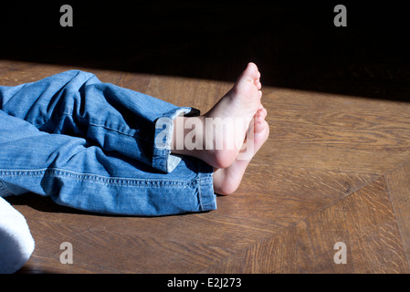 Barefoot child sitting on floor, low section - Stock Photo
