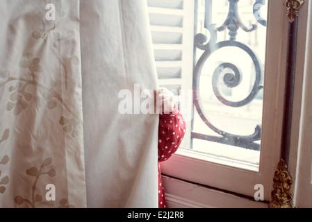 Child hiding behind curtain - Stock Photo