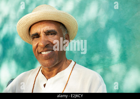 Portrait of retired senior hispanic man with straw hat sitting in park and looking at camera with happy expression - Stock Photo