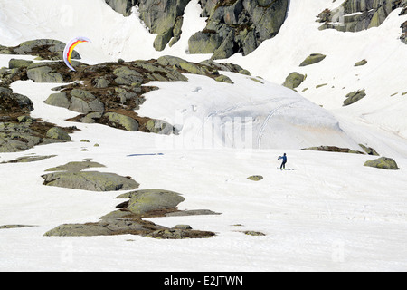 Snowkiting Skiiers skiing off piste on late snow in May on The Gotthard Pass or St. Gotthard Pass  Passo del San - Stock Photo