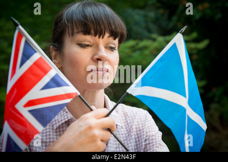 Young woman looking at a Scottish and British flag deciding how to vote in the Scottish independence referendum - Stock Photo