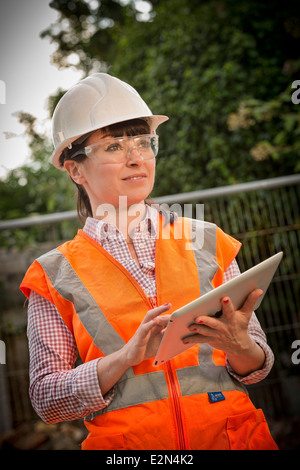 Female construction worker using an ipad - Stock Photo