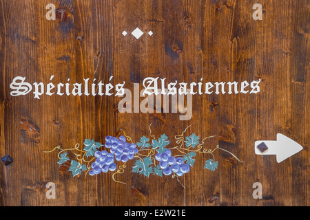 wooden sign displaying the text  spécialités alsaciennes  on the facade of a restaurant in eguisheim, alsace, france - Stock Photo