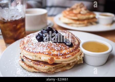 A stack of American style pancakes with blueberries. Served in a restaurant. - Stock Photo