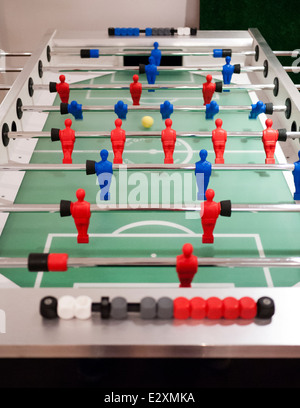 A game of fussball (table football) being played. Reds verses blues. - Stock Photo