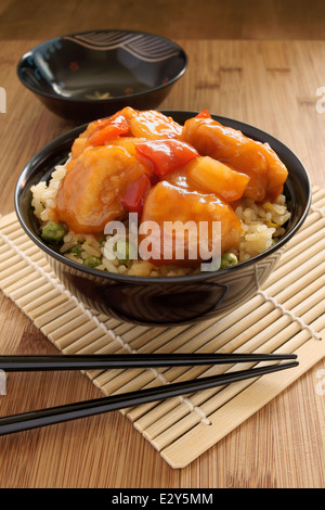 Sweet and sour chicken Cantonese style with egg fried rice in a lacquer bowl with chopsticks - Stock Photo