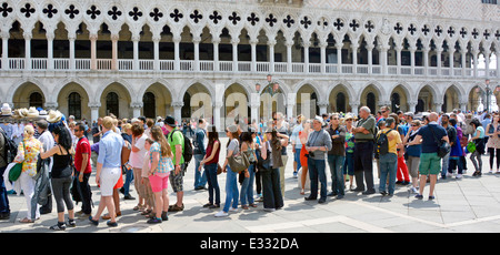 Doges Palace art museum & arches backdrop to queue group tourists people queuing hot summer sunshine for out of - Stock Photo