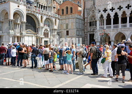 People & long queue of casually dressed summer tourists queuing waiting outside Italian Doges Palace towards historical - Stock Photo