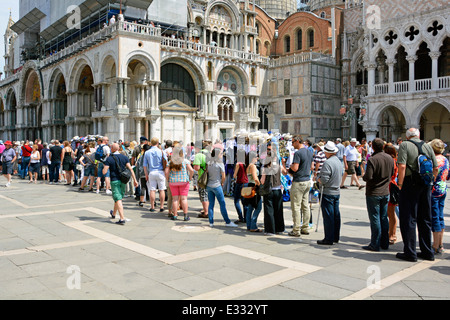 Long queue of casually dressed summer tourists people queuing & waiting outside Italian Doges Palace towards historical - Stock Photo