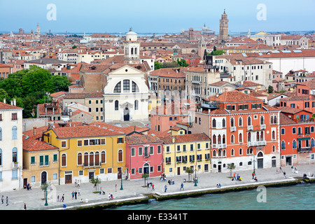 View from cruise ship departing Venice along the Giudecca Canal passing colourful waterside buildings - Stock Photo