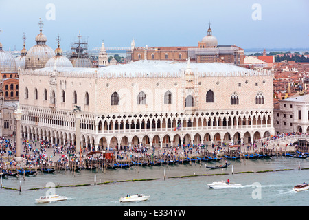 View from cruise ship departing Venice along the Giudecca Canal passing Doges Palace and row of moored gondolas - Stock Photo
