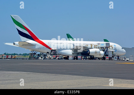 Emirates Airbus A380 double deck wide body four engine jet airliner parked on airport apron stand with ground crew - Stock Photo