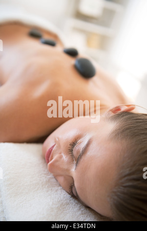 Relaxed young woman laying on massage table and receiving hot stone massage - Stock Photo