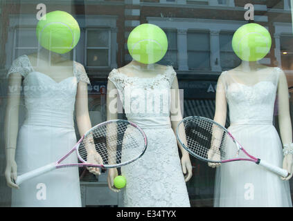 Wimbledon London, UK. 22nd June 2014. A shop  in Wimbledon  displaying models holding rackets with their heads as - Stock Photo