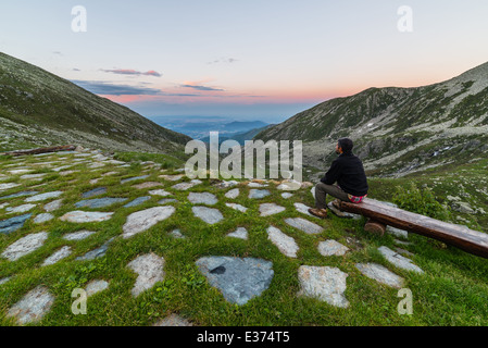 Male hiker sitting on a bench and looking at the view just after sunset. - Stock Photo
