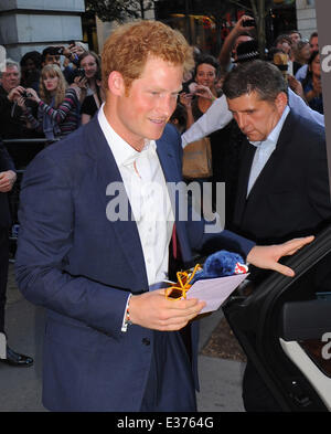 Prince Harry leaves Getty Images Gallery in London and was given a present by a fan for his new nephew Prince George. - Stock Photo