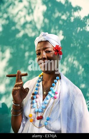 Portrait of african cuban woman smoking cohiba cigar and looking at camera smiling - Stock Photo