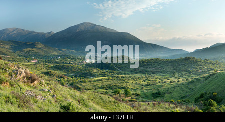Panoramic photograph of the sun rising and casing a warm light over the mountain and village at Agia Eirini, Kefalonia - Stock Photo