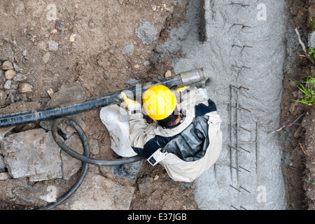Construction workers pour concrete into a ditch. Rainy weather. Bird's eye view. - Stock Photo