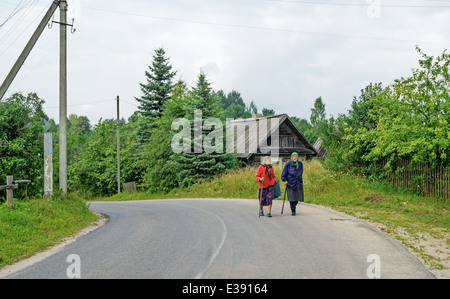 Rural summer lifestyle 2013. Grandmothers go on the asphalted highway passing through the village. - Stock Photo