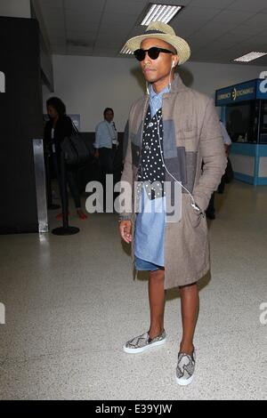 Pharrell Williams arrives at LAX in style. He wore a patchwork coat complimented by a polka dot waistcoat with long - Stock Photo