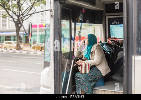 A passenger speaks on a mobile phone on a commuter bus in central Kuala Lumpur, Malaysia - Stock Photo