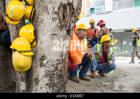 Migrant workers take a break from their work on a construction site in central Kuala Lumpur, Malaysia - Stock Photo
