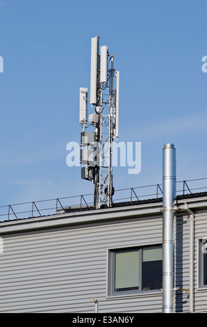 Antennas for mobile phone technology construction on modern house roof - Stock Photo