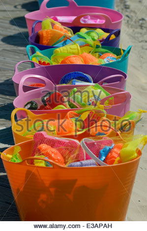 Row of brightly coloured trugs filled with children's buckets and spades on the beach at Weymouth, Dorset - Stock Photo