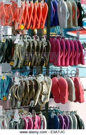 Hanging display of brightly coloured flip-flops for sale outside a shoe shop. - Stock Photo