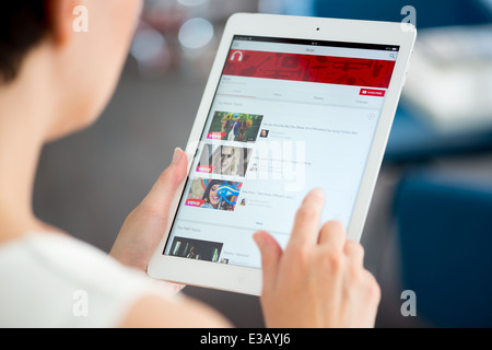 Woman holding a brand new Apple iPad Air and looking on YouTube music playlist on a screen - Stock Photo