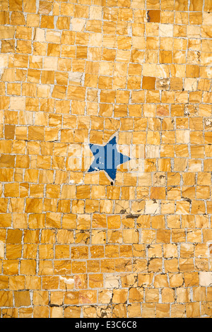 Detail of a ancient floor mosaic showing a blue five pointed star. - Stock Photo