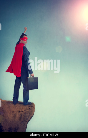 superhero businessman standing on a cliff edge pumping fist - Stock Photo