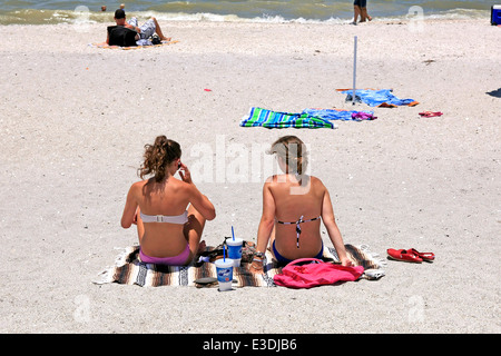 Two teenage girls sit in the hot sunshine on a Florida beach during Summer Vacation - Stock Photo